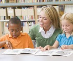 Teacher and Kdg Students Multiracial_Two-Students-In-Class-Reading--3917495